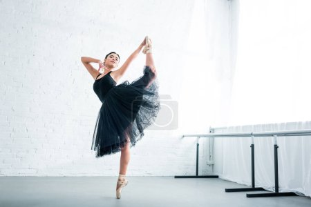full length view of beautiful young ballerina practicing ballet in studio