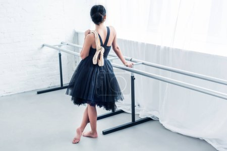 high angle view of young ballerina holding ballet shoes and looking away