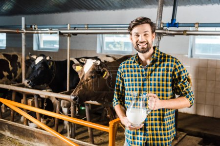 handsome farmer holding jug of milk in stable and looking at camera