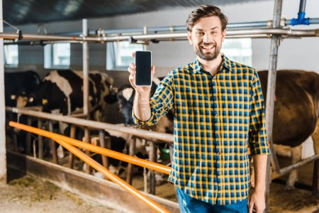handsome farmer showing smartphone with blank screen in stable