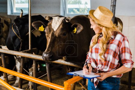 attractive farmer in straw hat holding clipboard and looking at cows in stable