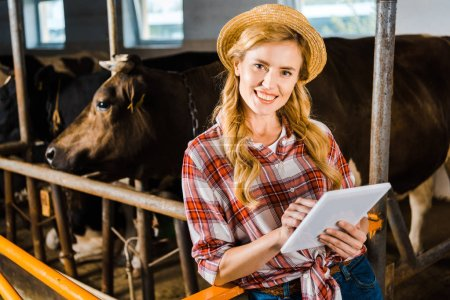 attractive farmer in straw hat holding tablet and looking at camera in stable