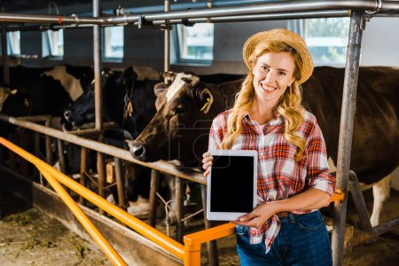 attractive farmer in straw hat showing tablet with blank screen in stable