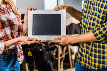 Photo pour Image recadrée d'agriculteurs montrant le tableau noir dans l'écurie - image libre de droit