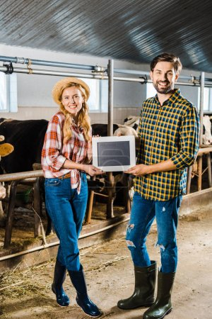Photo for Couple of smiling farmers showing blackboard in stable - Royalty Free Image