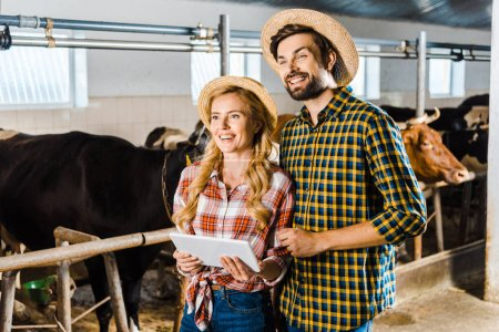 smiling couple of farmers with tablet looking away in stable