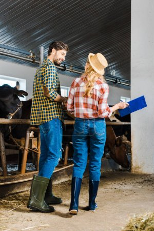 back view of couple of farmers standing in stable with clipboard