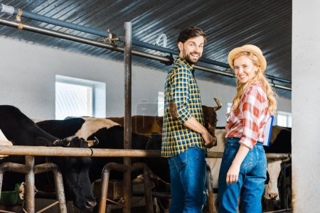Photo for Happy couple of farmers looking at camera in stable with cows - Royalty Free Image