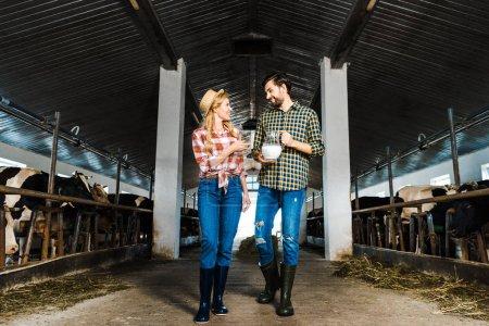 Photo pour Couple de paysans en regardant l'autre et tenant le pot de lait dans l'écurie - image libre de droit