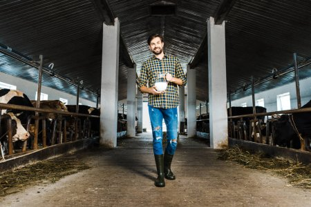 handsome farmer walking in stable with jug of milk