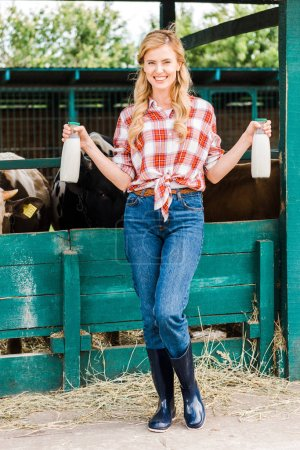 attractive farmer showing bottles of cow milk near stable