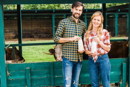 smiling couple of farmers holding bottles of cow milk near stable