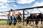 couple of happy farmers palming horse in stable