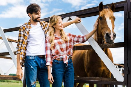 Photo for Couple of smiling farmers palming horse in stable - Royalty Free Image