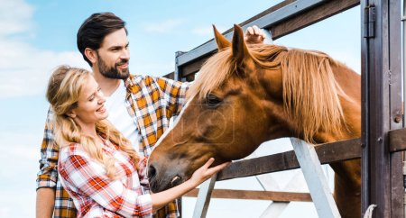 Photo for Couple of smiling ranchers palming horse in stable - Royalty Free Image