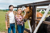 couple of smiling ranchers palming horse in stable and looking at camera