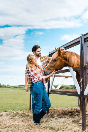 couple of happy ranchers palming horse in stable