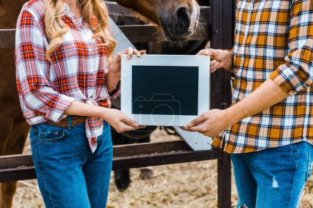 Photo for Cropped image of couple of farmers holding blackboard in stable - Royalty Free Image
