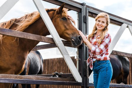 beautiful farmer palming brown horse in stable and looking at camera