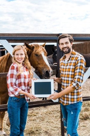 Photo for Happy couple of farmers holding blackboard in stable - Royalty Free Image