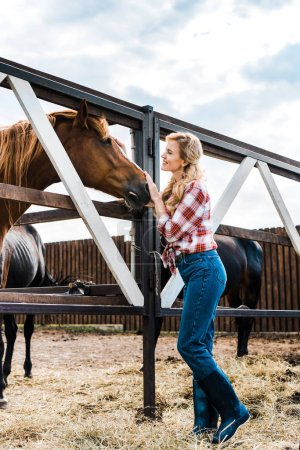 Photo for Side view of attractive smiling farmer palming horse in stable - Royalty Free Image