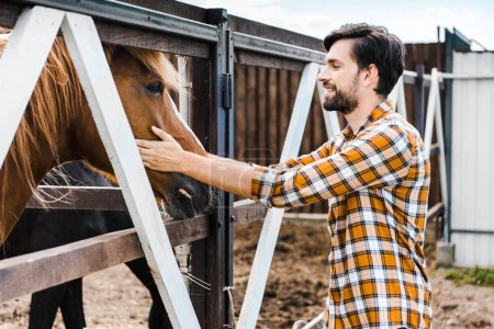 side view of handsome smiling farmer palming brown horse in stable