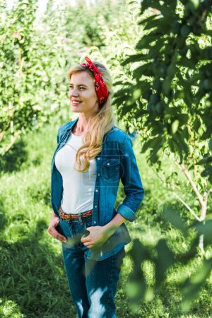 attractive farmer looking away in green garden at farm