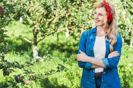 smiling attractive farmer standing with crossed arms in apple garden