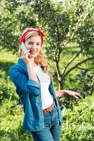 smiling attractive farmer talking by smartphone in apple garden at farm