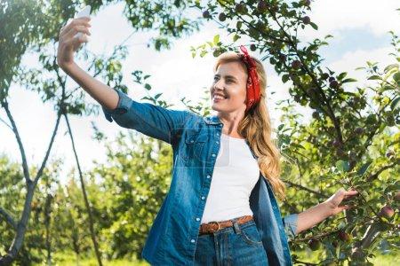 Photo pour Séduisante agriculteur prenant selfie smartphone dans le jardin de la pomme à la ferme - image libre de droit