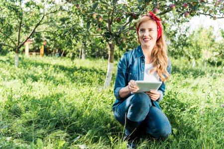 Photo pour Agriculteur attrayant s'accroupissant et en tenant la tablette dans le jardin de la pomme à la ferme - image libre de droit
