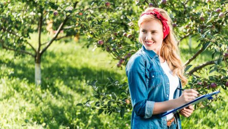 smiling farmer holding clipboard in apple garden at farm and looking away