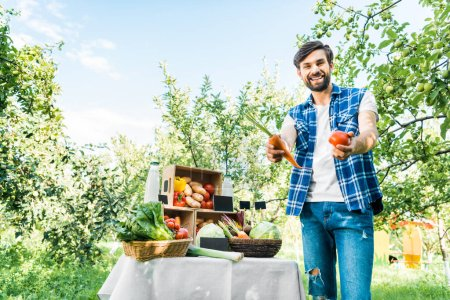 happy farmer showing ripe ecological vegetables at farmer market