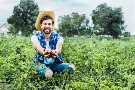 handsome happy farmer showing ripe potatoes in hands in field
