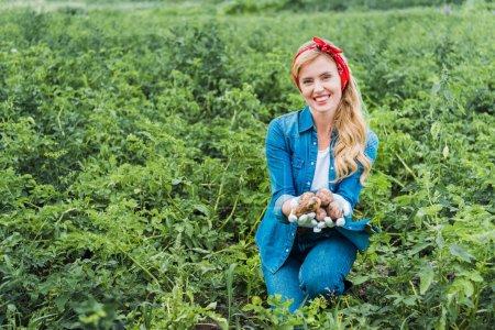 attractive farmer showing ripe potatoes in field at farm