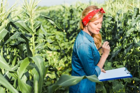 beautiful farmer checking harvest with clipboard in field at farm