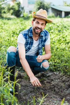 Happy handsome farmer planting cardamom seeds in field at farm