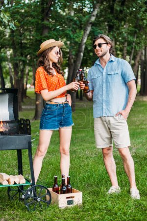 stylish couple clinking bottles of beer during bbq in park
