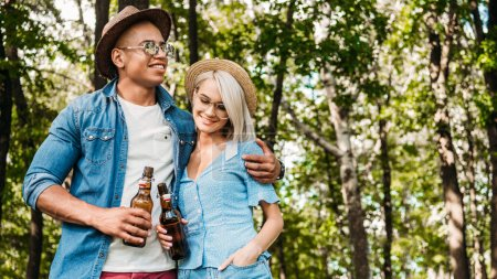 Photo for Portrait of smiling multiracial couple with beer in summer park - Royalty Free Image