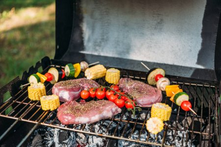 close up view of meat and vegetables cooking on grill zucchini
