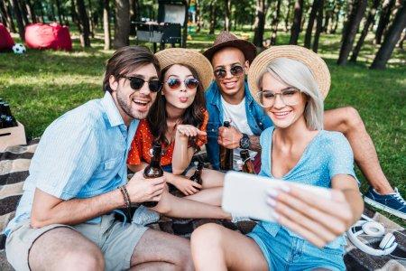 Photo pour Amis multiculturelles souriants avec de la bière en tenant selfie sur smartphone tout en se reposant dans le parc de l'été - image libre de droit