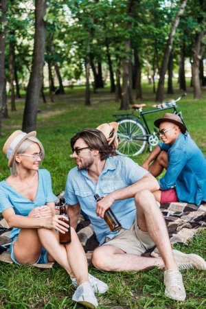 Photo for Multiracial friends with beer resting in summer park - Royalty Free Image