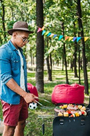 side view of african american man in sunglasses and hat cooking food on grill in park