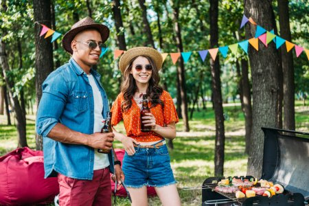 smiling interracial young couple with beer standing near grill in summer park