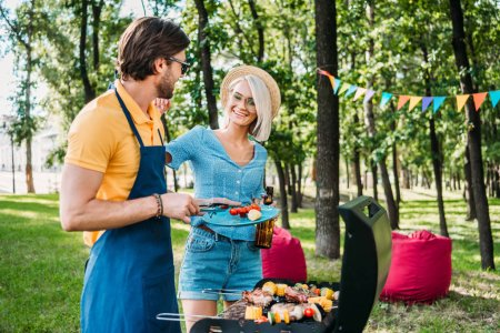 cheerful couple having barbecue in summer park