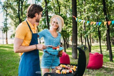 Joyeux couples ayant le barbecue dans le parc de l'été