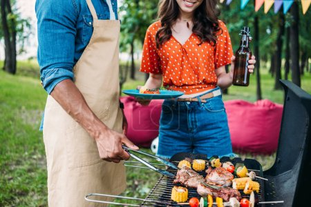 partial view of woman with beer looking at african american boyfriend cooking food on grill during barbecue