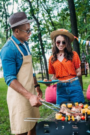 smiling woman with beer looking at african american boyfriend cooking food on grill during barbecue