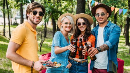 portrait of young multiethnic friends having barbecue in summer park