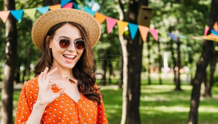 portrait of happy young woman in hat and sunglasses showing ok sign in park